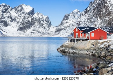 Red fisherman´s house on Lofoten islands in front of a fjord at a beautiful sunny winter day