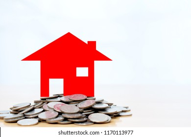 Red house sitting on a stack coins