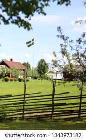 A red house and the Swedish flag in summer. Typical Swedish landscape.