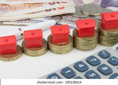 A red houses sitting on a coins, with a pen and calculator to symbolize house finance in the U.k.