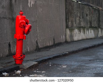 A red hydrant on a street. Both the road and the background wall are very gray contrasting with the fire hydrant. Some dirt on the hydrant and also some show around