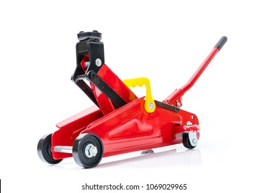 Red hydraulic floor jack isolated on white background.