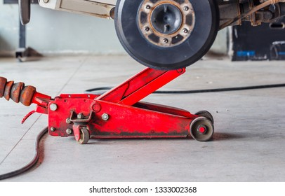 Red hydraulic floor lift jack for repairing the undercarriage