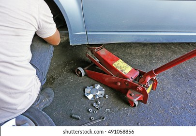 red hydraulic jack in use. a male mechanic performing maintenance work on a car.