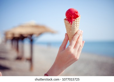Red ice cream in hand on the sea. Concept of sweet rest.