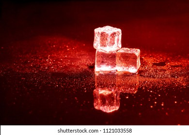 Red ice cubes reflection on black table.