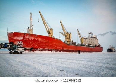 A red icebreaker stands on unloading in the ice of the Arctic.