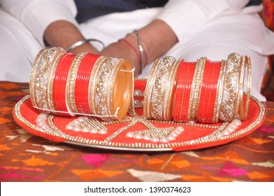 Red Indian wedding bangles, man sits in the background.