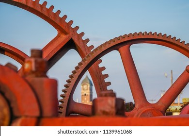 Red industrial gears with nineteenth century brick mill building in background