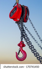 red Industrial hook hanging on reel chain and blue sky sunset background