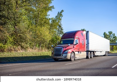 Red industrial long haul big rig semi truck with high cabin transporting frozen cargo in refrigerator semi trailer driving on the wide multiline interstate highway road with trees on the side