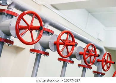 Red industrial valves in a row on gray pipelines system