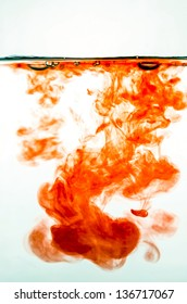 Red ink in colored water on white background.