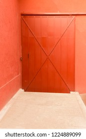 Red iron door and sliding rail with safety lock - Orange wall and concrete floor