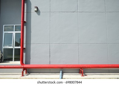 Red iron plumbing fixtures on gray concrete walls to send water to the rooms in the building. Acts like a vein in the human body.