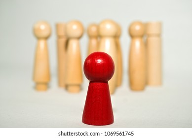 red isolated wooden figure in the foreground, blurred wooden figures in the background, systemic board, family therapy