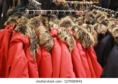 red jackets with a fake fur collar hanging in a row in a store
