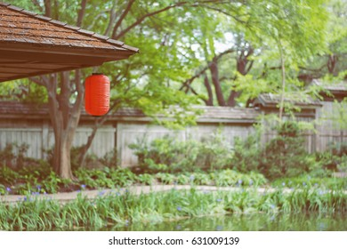a red Japanese lantern hanging on the wooded roof  with green trees background, filtered tones