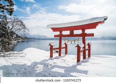 A red Japanese Torii in front of lake Tazawa, Akita prefecture, Japan