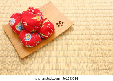 Red Japanese traditional toy Otedama bean bags put on wooden plate with Tatami flooring mat in the background