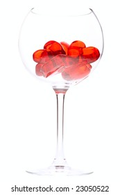 red jelly hearts in wine glass over white background