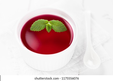 Red jelly in white bowl garnished with mint leaves (Selective Focus, Focus on the big mint leaves)