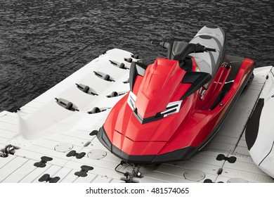 Red jet ski parked beside the sea on black and white scene