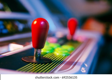 Red Joystick of an Old Arcade Video Game with Blurred Background