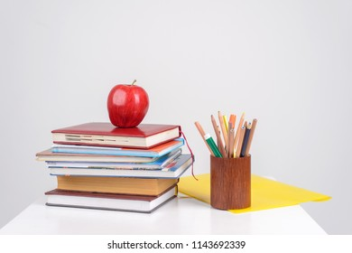 red juicy apple lies on a pile of training books on the table, beside it there are multicolored pencils, pens and markers in the stand and the yellow folder lies
