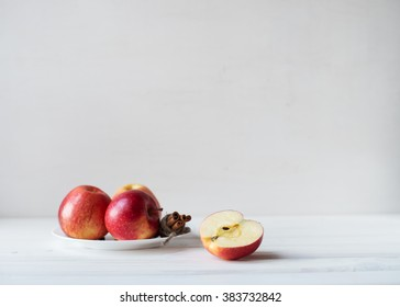 The red juicy apples and cinnamon sticks on a plate. Half of apple on a wooden table.