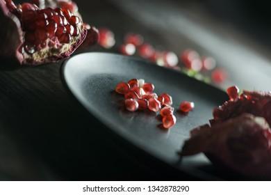 Red juicy pomegranate on black slate plate.