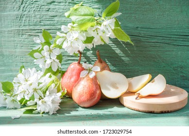 Red juicy ripe pears and white flowers on a branch on a green wooden table. Vegetarian food. Beautiful still life