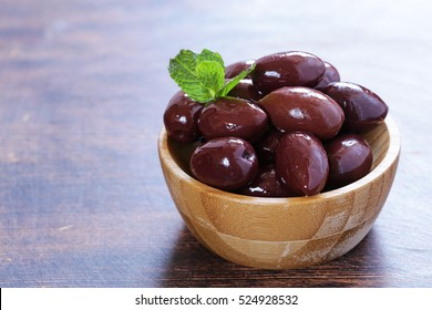 red kalamata olives on a wooden table