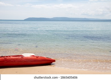 Red kayak boat staying on the beach with sunny day.
