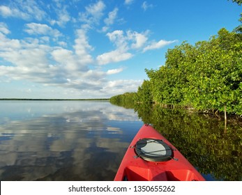 Red kayak on Coot Bay amidst mangroves and reflected clouds in Everglades National Park, Florida.