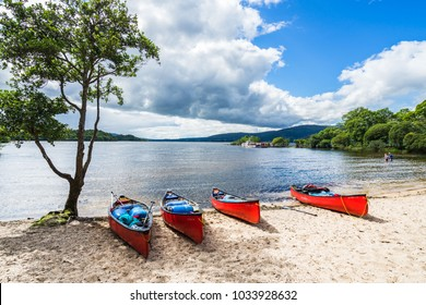 Red kayaks on a sandy beach in the summer. Loch Lomond, Scotland, Britain, August 2017