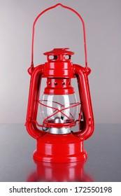 Red kerosene lamp on grey background