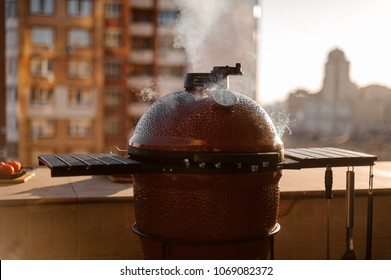 Red kettle barbecue grill closed and covered with lid and equipped with cooking tools standing on the roof and cooking a dish