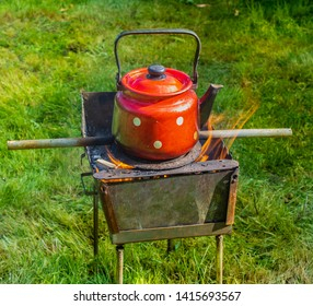 Red kettle on an open fire on a green lawn. Side view. Long stick The concept of survival in the absence of traditional sources of energy. Irony or joke.Heating the water in the old kettle