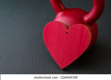 Red kettlebell on a black gym floor with large red heart to celebrate Valentine's Day fitness