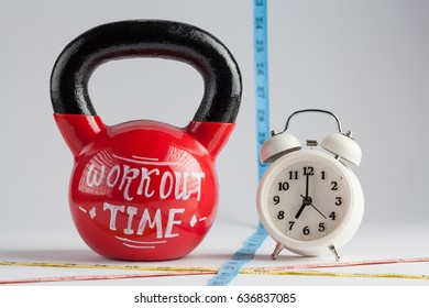 Red kettlebell with Workout Time lettering, traditional alarm clock, and measuring tape isolated on white with copy space. Time to work out, healthy lifestyle and diet concept