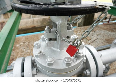 Red key lock and chain to prevent the valve being opened is part of the Lock out tag out system in oil and gas plant.