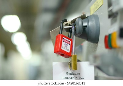 Red key lock and white tag for process cut off electrical on control panel in substation at chemical plant. Thai language in label language translator that isolation tag. (Do not remove this tag)