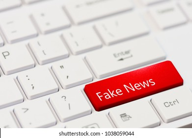 Red key with text Fake News and icon on white laptop keyboard.