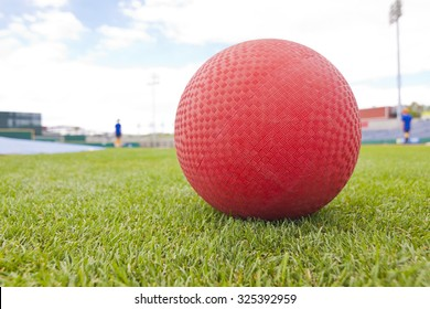 Red Kick Ball on grass field, low angle