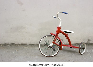 Red Kids Bicycle in a Poor Street