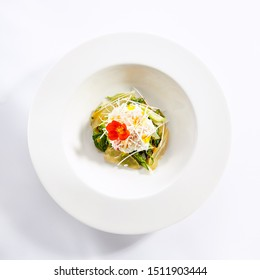 Red king crab with spinach and pear top view. Seafood dish with fruit and herb isolated on white background. Served delicious food composition. Prepared restaurant gourmet meal in plate