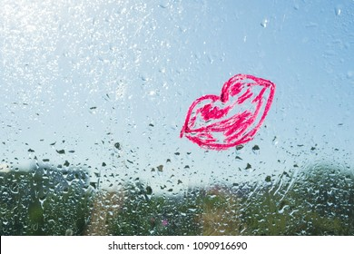 Red kiss lips painted with lipstick on the window with water drops. Background blue sunny sky, drops shine in the sun