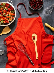 Red kitchen apron on black chalkboard background. Top view. Strawberries and cherries on a dark background. Apron and berries. Space for text. The summer berries. Preparation of baking from berries.