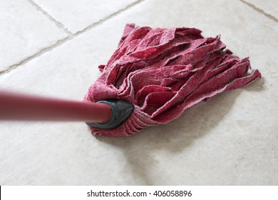 Red kitchen mop being used to clean a floor surface
